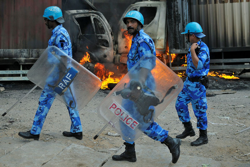 Members of the security forces make their way past burning lorries in Bengaluru, which were set on fire by protesters after India's Supreme Court ordered Karnataka state to release 12,000 cubic feet of water per second every day from the Cauvery river to neighbouring Tamil Nadu, India, on September 12, 2016. Photo: Reuters