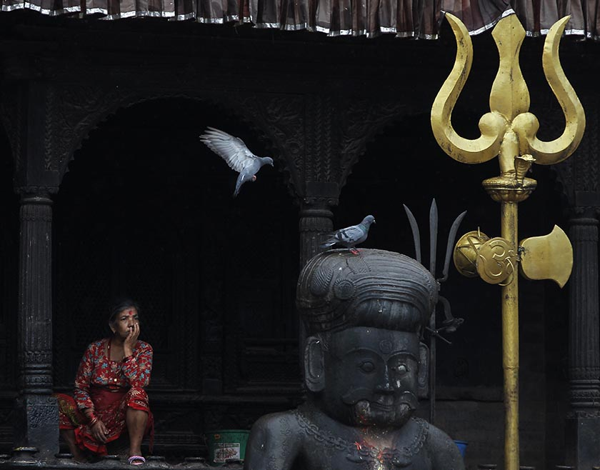 Pigeons land on a statue as a Nepali woman takes rest at the Dattatreya Temple in Bhaktapur, Nepal, Monday, Sept. 12, 2016. Bhaktapur, also known as the city of devotees, is an ancient city popular for its traditional architectural buildings, temples and unique festivals. Photo: AP