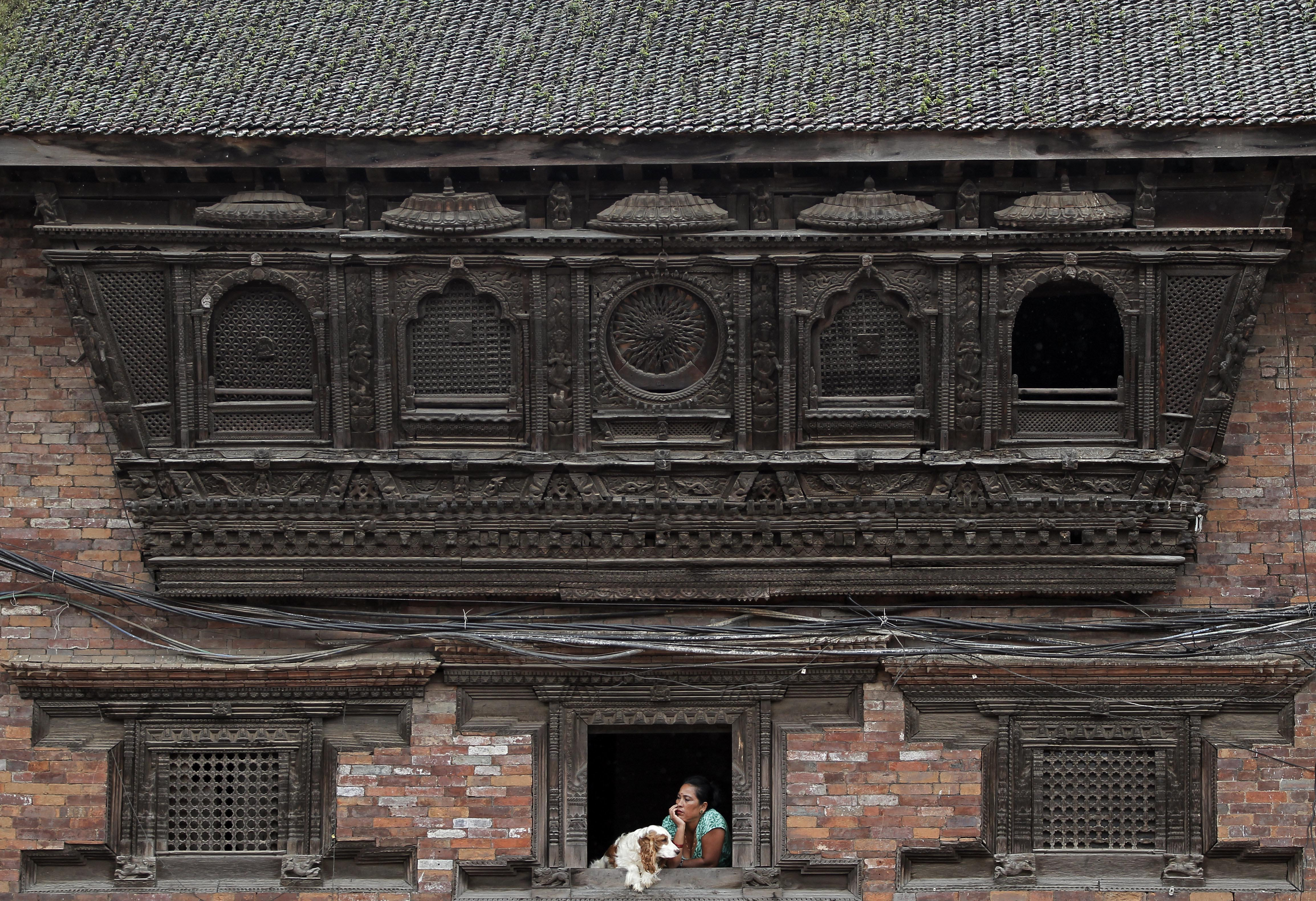 A Nepali woman sits with her dog and watches outside from an artistically crafted wooden window in Bhaktapur, Nepal, Monday, Sept. 12, 2016. Bhaktapur, also known as the city of devotees, is an ancient city popular for its traditional architectural buildings, temples and unique festivals. Photo: AP