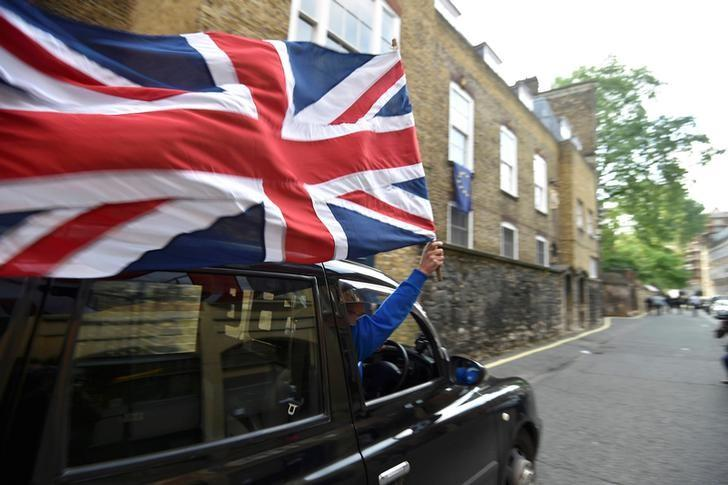 A taxi driver holds a Union flag, as he celebrates following the result of the EU referendum, in central London, Britain June 24, 2016.    REUTERS/Toby Melville/Files