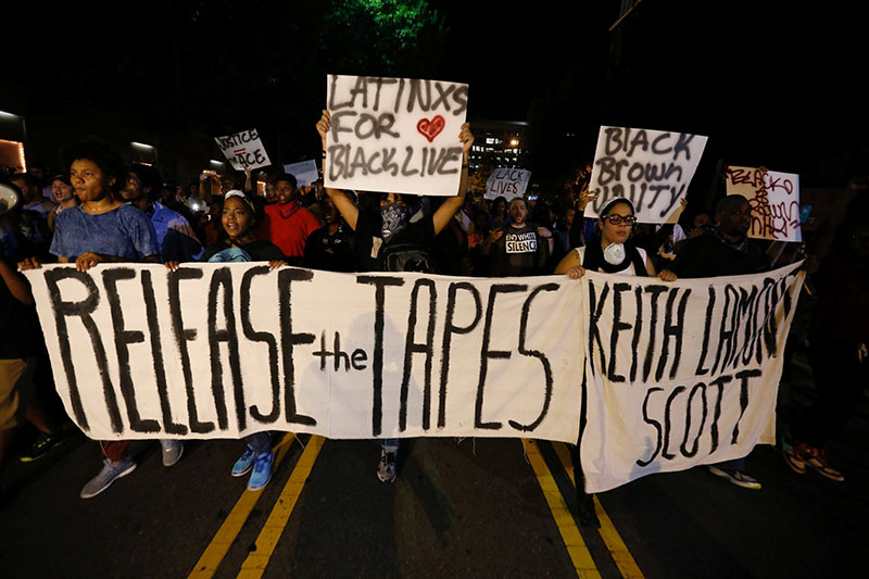 Protesters hold signs while marching to demonstrate against the police shooting of Keith Scott in Charlotte, North Carolina, US, on September 23, 2016. Photo: Reuters
