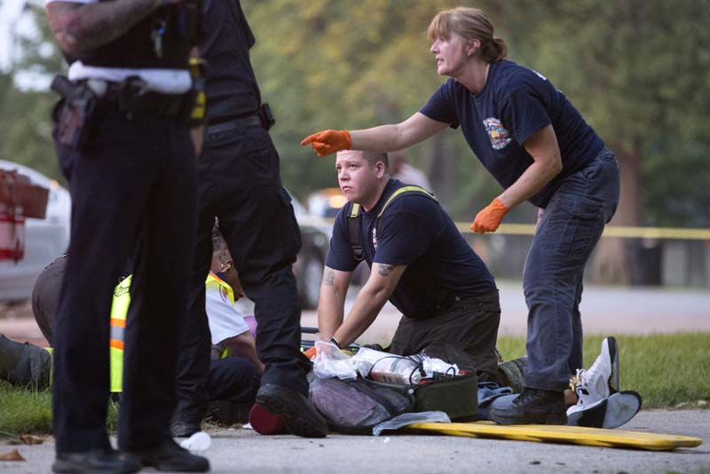 File- Members of the Chicago Fire Department work on a gunshot victim at the scene of a double shooting in Ogden Park, on Monday, September 5, 2016. Photo: AP