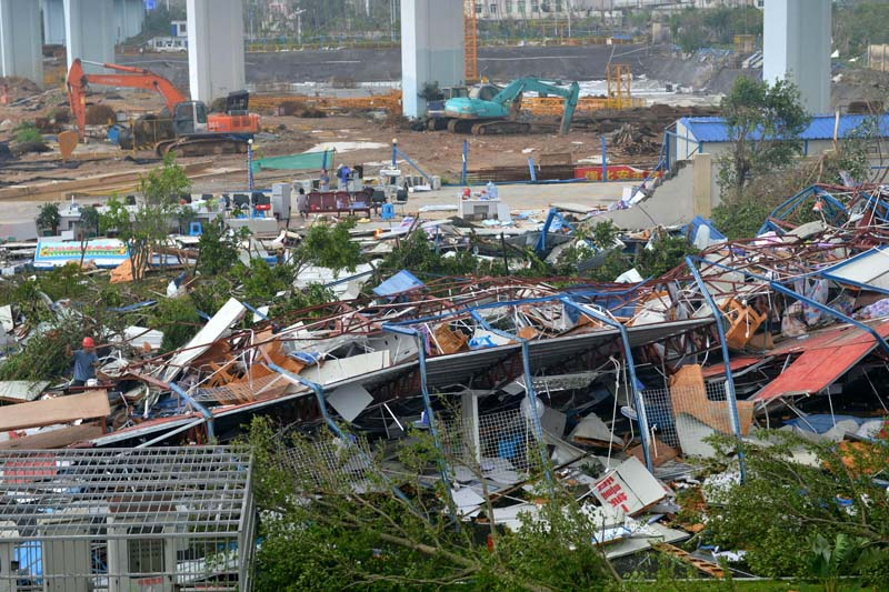 A man wearing a red helmet (L) climbs on the wreckage of a destroyed structure after a typhoon in Xiamen in southeastern China's Fujian province, on September 15, 2016. Photo: AP