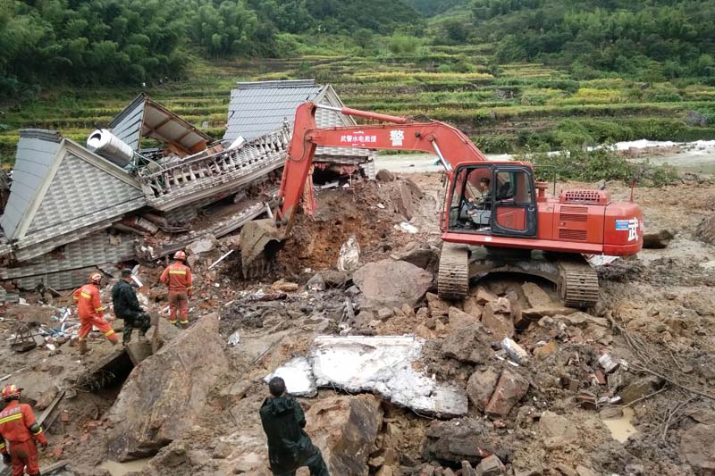 Rescuers use heavy equipment to dig in the rubble of a house that was destroyed in a landslide in Sucun village in eastern China's Zhejiang Province, on Thursday, September 29, 2016. Photo: AP