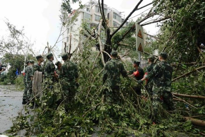 Paramilitary policemen remove toppled trees after Typhoon Meranti swept through Xiamen, Fujian province, China, September 15, 2016. REUTERS/Stringer