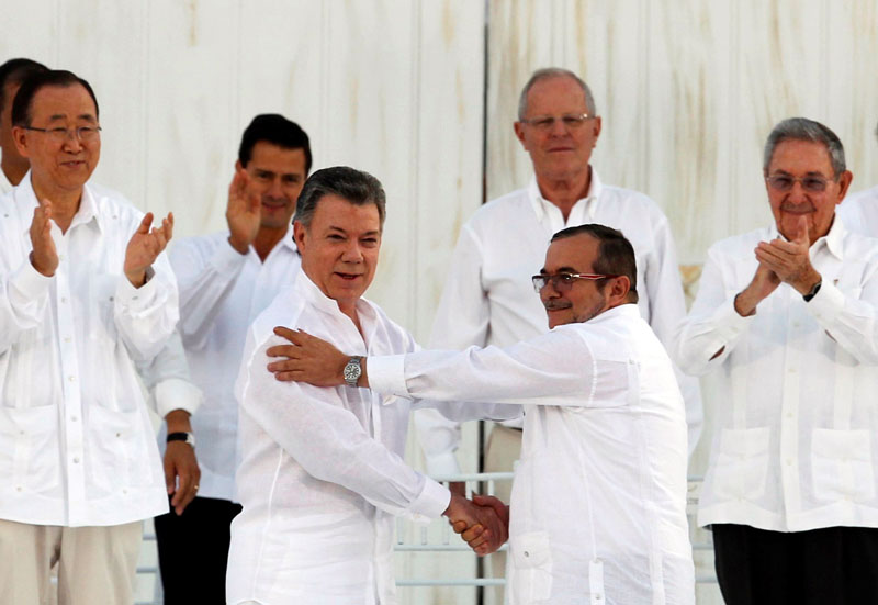 Colombian President Juan Manuel Santos (left) and Marxist rebel leader Rodrigo Londono (right), better known by the nom de guerre Timochenko, shake hands after signing an accord ending a half-century war that killed a quarter of a million people in Cartagena, Colombia, on September 26, 2016. Photo: Reuters