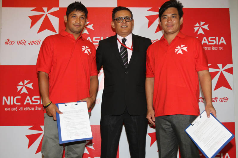 Cricketers Raju Rijal (left) and Prem Tamang with NIC Asia Bank CEO Laxman Risal after signing the MoU in Kathmandu on Thursday, September 2, 2016. Photo: THT