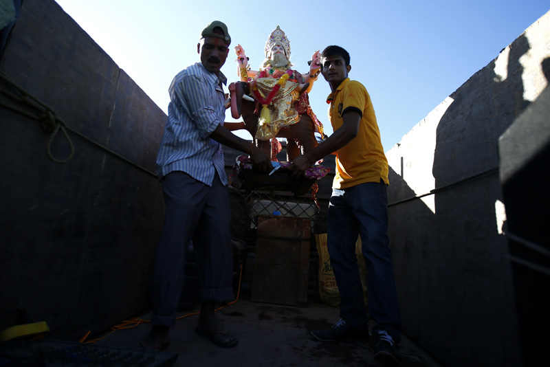 Hindu Devotees carry the idol of Lord Bishwakarma from a vehicle before they immerse the idol of Lord Bishwakarma into the Bagmati River so as to conclude the Bishwakarma Pooja festival, near Taudaha of Kathmandu, on Sunday, September 18, 2016. It is believed that the immersed idol reaches India flowing through the river. Photo: Skanda Gautam