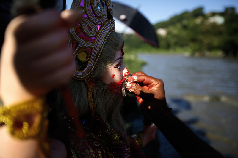 A Hindu Devotee (face unseen) feeds the idol of Lord Bishwakarma as part of prayers before immersing the idol of Lord Bishwakarma into the Bagmati River so as to conclude the Bishwakarma Pooja festival, near Taudaha of Kathmandu, on Sunday, September 18, 2016. It is believed that the immersed idol reaches India flowing through the river.  Photo: Skanda Gautam