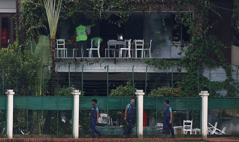 File - Policemen patrol outside the Holey Artisan Bakery and the O'Kitchen Restaurant as others inspect the site after gunmen attacked, in Dhaka, Bangladesh, on July 3, 2016. Photo: Reuters