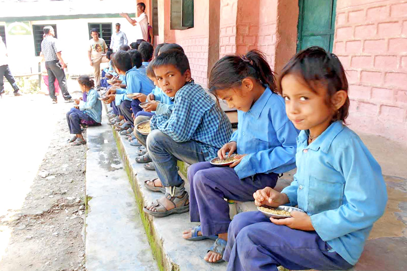 Students of Janata Primary School enjoying their afternoon snacks in Dadeldhura district, on Thursday, September 29, 2016. The number of students in the school has surged significantly after launching Food for Education programme in the district. Photo: RSS