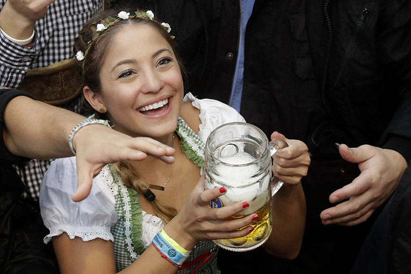 A young woman smiles with a beer during the opening of the 183rd Oktoberfest beer festival in Munich, southern Germany, on Saturday, September 17, 2016. The world's largest beer festival will be held from September 17 to October 3, 2016. Photo: AP