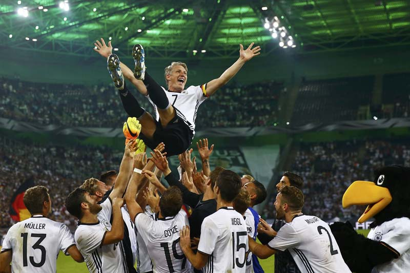 Germany's Bastian Schweinsteiger gets honoured by his teammates after their friendly match with Finland in Moenchengladbach, Germany on August 31, 2016. Photo: Reuters
