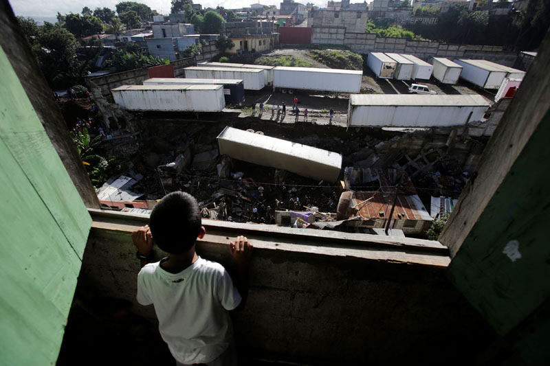 A child looks at the site where a landslide took place causing a trailer to fall on top of homes causing several casualties in Villanueva, on the outskirts of Guatemala City, Guatemala, on September 7, 2016. Photo: Reuters