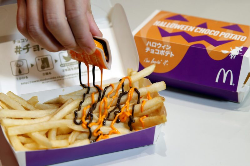 An employee of McDonald's Japan puts pumpkin and choco sauce on a McFry Potato to demonstrate their company's 'Halloween Choco Fries - Pumpkin & Choco Sauce' in Tokyo, Japan, on September 29, 2016. Photo: Reuters