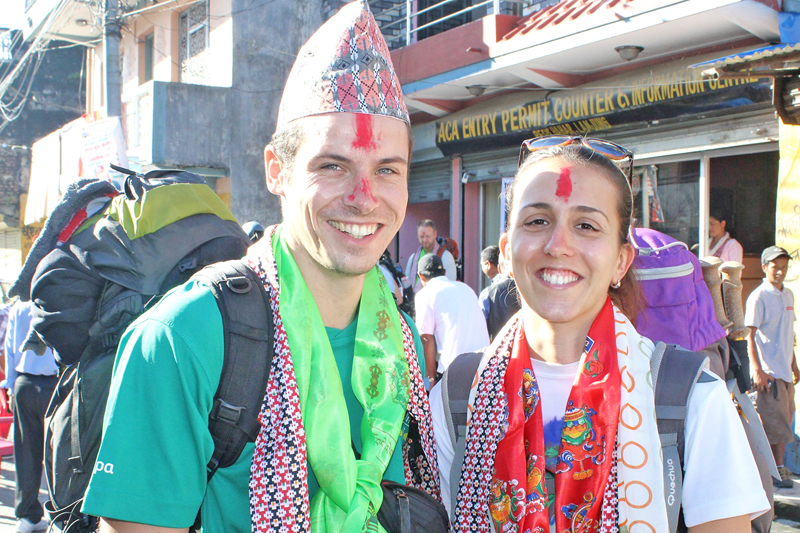 An euphoric looking foreign couple, one of them don in Nepalitopi, pose for a photo at Besishahar of Lamjung on Tuesday, September 27, 2016. Photo: RSS