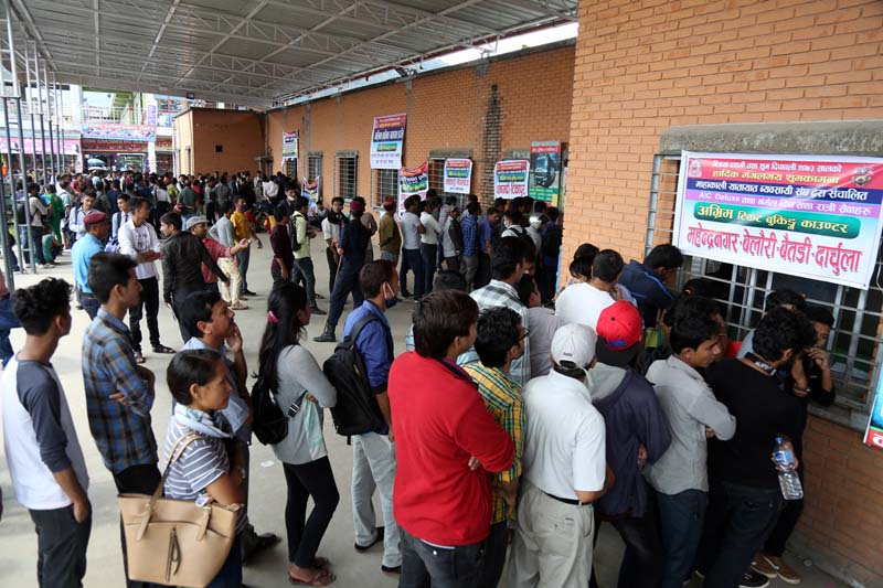 People stand in line while some crowd around, to buy tickets to go home for the upcoming Dashain festival, at the Naya Bus Park ticket counter, Gongabu, on Friday, September 23, 2016. Photo: RSS