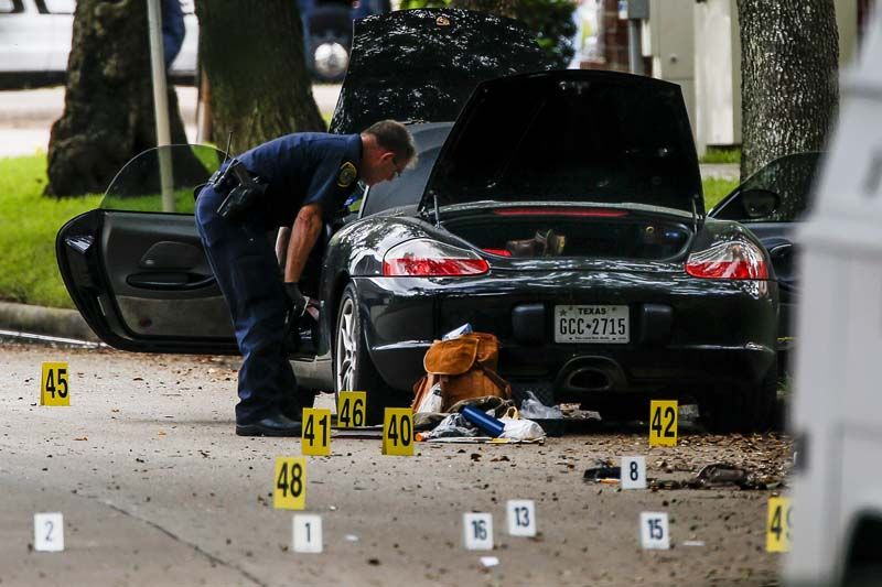 A police officer investigates a car belonging to local lawyer, Nathan Desai, who shot and injured multiple people before he was killed by police at Law Street at Weslayan in Houston, on Monday, September 26, 2016. Photo: AP