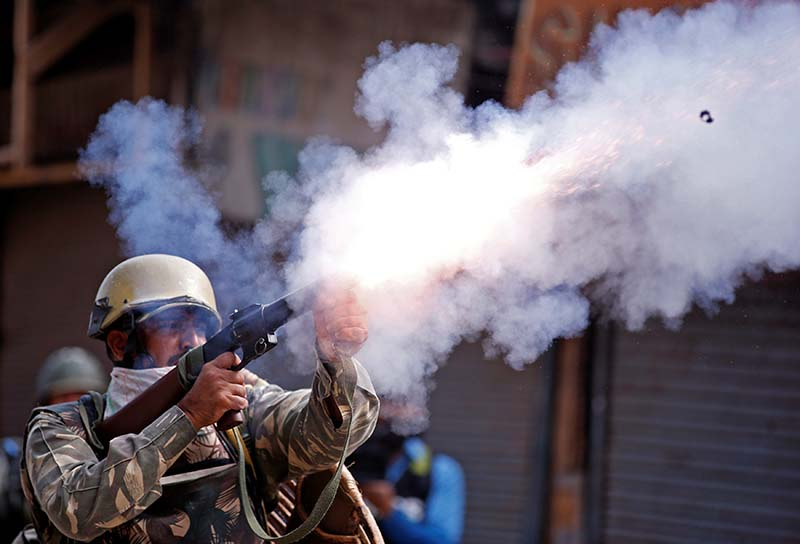 An Indian policeman fires a teargas shell towards demonstrators during a protest against the recent killings in Kashmir, in Srinagar, on Tuesday, September 13, 2016. Photo: Reuters