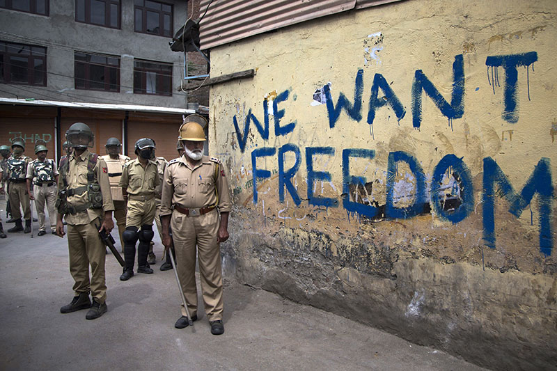 FILE - Indian policemen stand guard during a curfew in Srinagar, Indian-controlled Kashmir, on August 12, 2016. Photo: AP