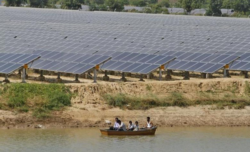 Security personnel sit in a boat as they patrol the premises of a newly inaugurated solar farm at Gunthawada village in Banaskantha district in Gujarat October 14, 2011. Photo: Reuters