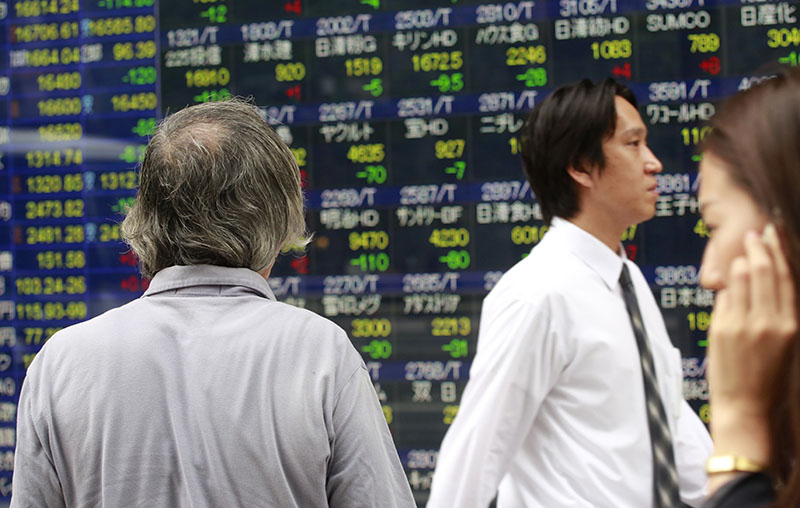 A man looks at an electronic stock indicator of a securities firm in Tokyo, on Wednesday, September 14, 2016. Photo: AP