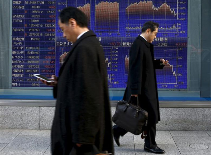 Men walk past an electronic board showing market indices outside a brokerage in Tokyo, Japan, March 2, 2016. Photo: Reuters