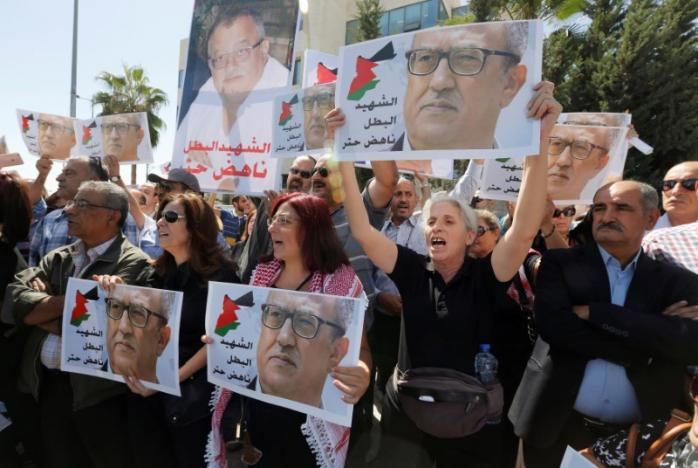Relatives and activists hold pictures of the Jordanian writer Nahed Hattar, who was shot dead, and shout slogans during a sit-in in front of the prime minister's building in Amman, Jordan, September 26, 2016. REUTERS/Muhammad Hamed