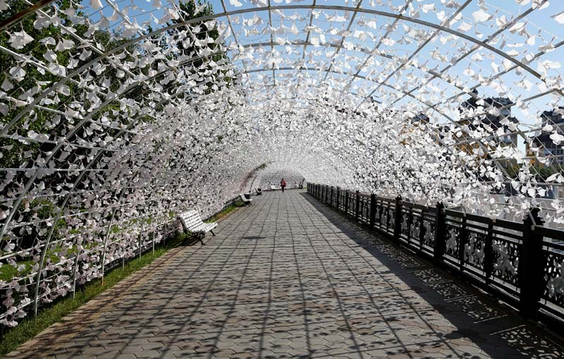 A woman walks along the decorated embankment of the Ishim river in Astana, Kazakhstan, on September 5, 2016. Photo: Reuters