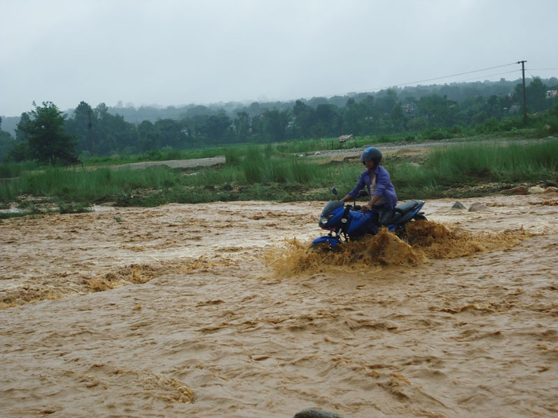 A motorcycle is seen struggling with the water flown from the flooded Kukhreni Khola, which borders wards 9 and 14 of Hetaunda Sub-metropolitan City, on Sunday, September 4, 2016. Photo: Prakash Acharya