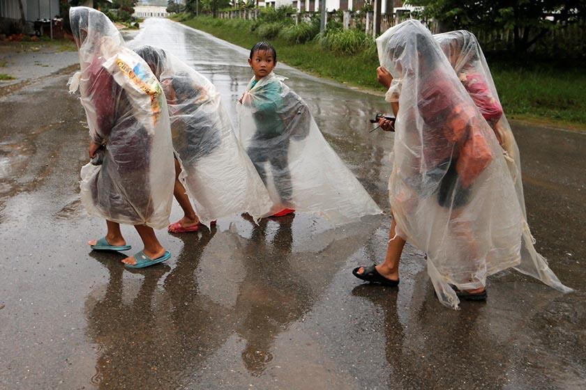 Children walk under the rain in the northen city of Xieng Khouang, Laos September 3, 2016. REUTERS/Jorge Silva
