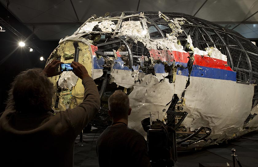 FILE - In this Tuesday, Oct. 13, 2015 file photo, journalists take images of part of the reconstructed forward section of the fuselage after the presentation of the Dutch Safety Board's final report into what caused Malaysia Airlines Flight 17 to break up high over Eastern Ukraine last year, killing all 298 people on board, during a press conference in Gilze-Rijen, central Netherlands. Relatives of victims of the shooting-down of a Malaysia Airlines jetliner over Ukraine more than two years ago were gathering Wednesday, Sept. 28, 2016 to learn the preliminary results of a Dutch-led criminal probe of the disaster that claimed 298 lives.  (AP Photo/Peter Dejong, File)