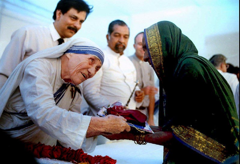 Mother Teresa presents documents for a new house to a villager from Latur in Bombay on September 26, 1994. REUTERS/Savita Kirloskar