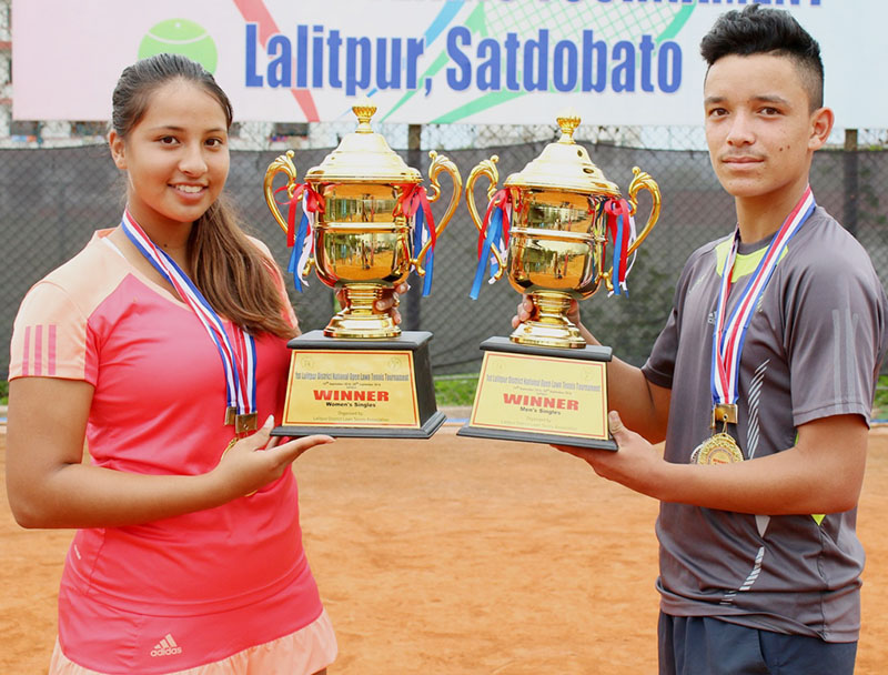 Mayanka Rana and Samrakshyak Bhushan Bajracharya hold the trophies after winning the first National Open Lawn Tennis Tournament in Lalitpur on Wednesday, September 28, 2016. Photo courtesy: NSC