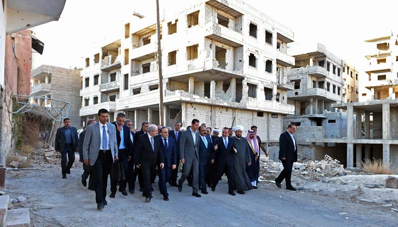File- Syrian President Bashar Assad (C) walks on a street with officials after performing the morning Eid al-Adha prayers in Daraya, a blockaded Damascus suburb, Syria, on September 12, 2016. Photo: AP