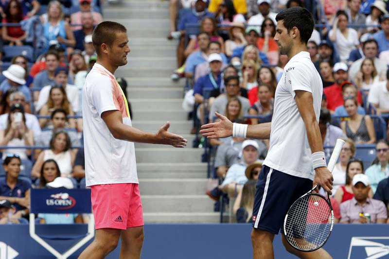 Mikhail Youzhny of Russia (left) shakes Novak Djokovic's hand upon retiring from their match in the first set during the third round of the US Open tennis tournament, on Friday, September 2, 2016, in New York. Photo: AP