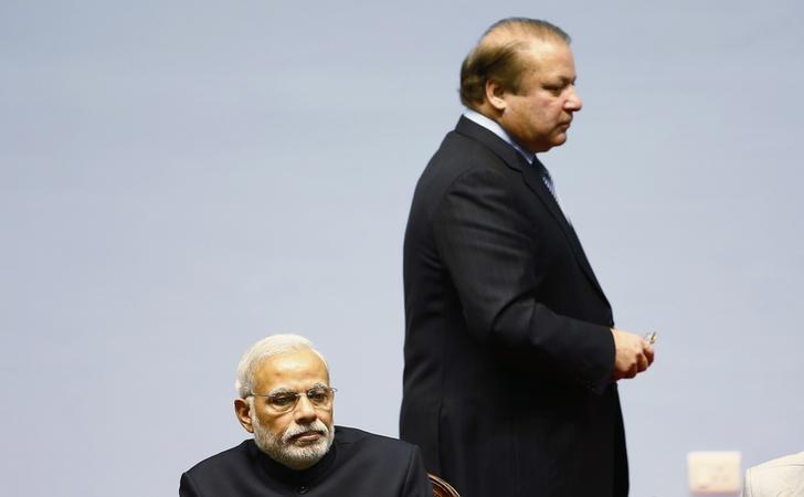 Pakistani Prime Minister Nawaz Sharif walks past his Indian counterpart Narendra Modi (foreground) during the opening session of 18th South Asian Association for Regional Cooperation (SAARC) summit in Kathmandu November 26, 2014. REUTERS/Narendra Shrestha/Pool/Files