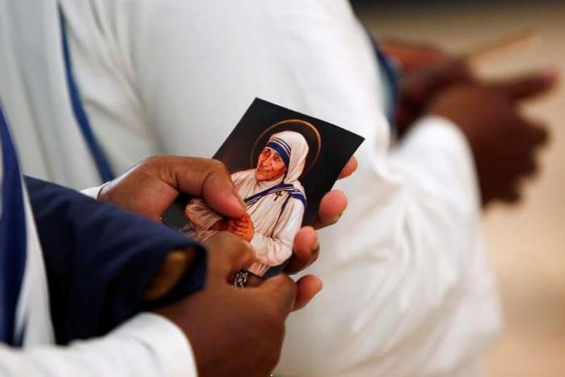 A nun from the members of Mother Teresa's order, the Missionaries of Charity, holds a prayer card during the unveiling an official canonisation portrait of Mother Teresa at the John Paul II National Shrine in Washington, US, on September 1, 2016. Photo: Reuters