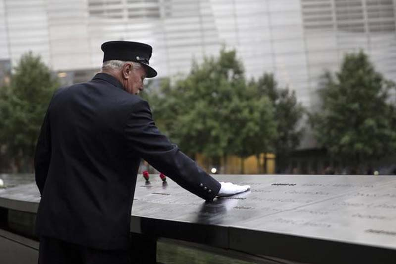 A member of the New York Fire Department places his hand on the memorial before a ceremony marking the 15th anniversary of the 9/11 attacks, at the National September 11 Memorial and Museum in Lower Manhattan in New York, on September 11, 2015. Photo: Reuters
