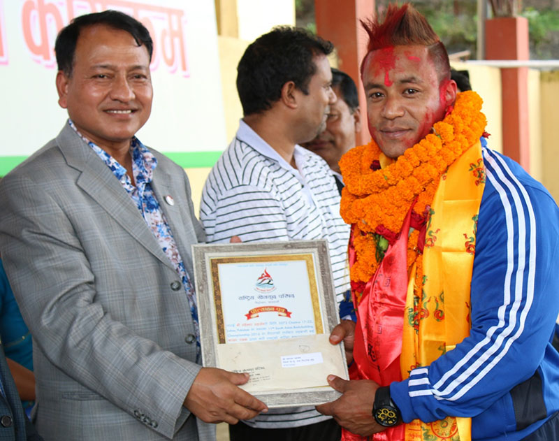 National Sports Council Member Secretary Keshab Kumar Bista handing over a felicitation letter to Maheshwor Maharjan, who won the 75kg weight category gold medal in the 50th Asian Bodybuilding Championship in Bhutan on Tuesday, September 6, 2016. Photo: THT