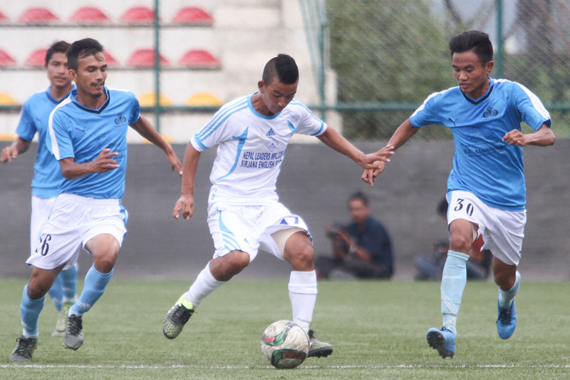 A player of Nayabasti Youth Club (centre) dribbles the ball past Chyasal Youth Club players during their Martyrs Memorial B Division League match in Lalitpur on Friday. THT