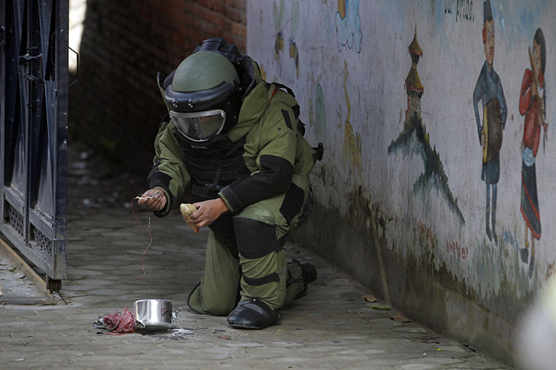 A Nepali bomb squad member inspects a pressure cooker bomb after detonating it at the school in  Kathmandu, on Tuesday, September 20, 2016. Photo: AP