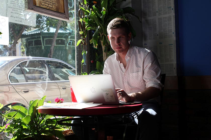 Reuters journalist Nick Brown works at his laptop at a cafe in San Juan, Puerto Rico, August 8, 2016. Picture taken August 8, 2016. REUTERS/Alvin Baez