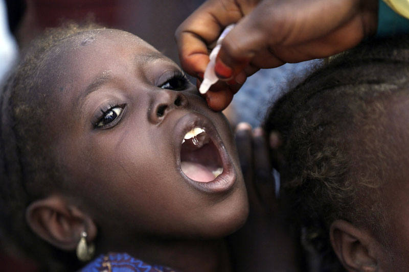A health official administers a polio vaccine to a child at a camp for people displaced by Islamist Extremists, in Maiduguri, Nigeria, on Sunday, August 28, 2016. Photo: AP
