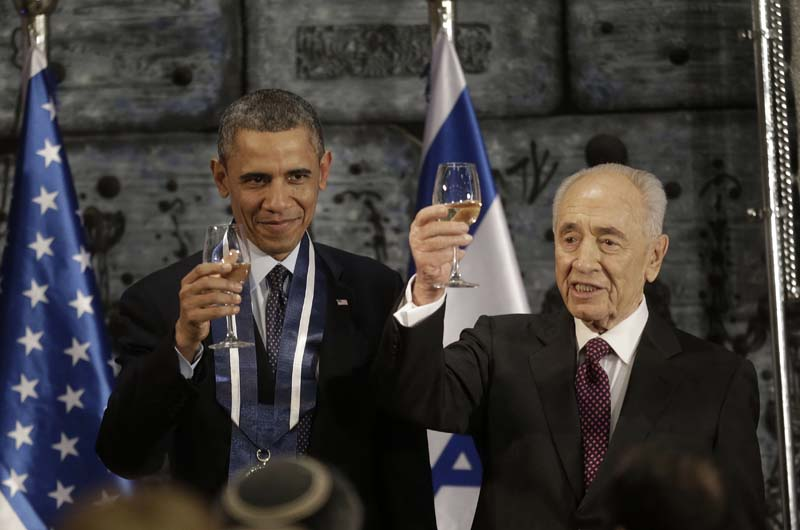 File- US President Barack Obama and Israeli President Shimon Peres raise their glasses in a toast after Obama received the Israeli Medal of Distinction from Peres during a State Dinner at President's residence in Jerusalem, Israel, on March 21, 2013. Photo: AP