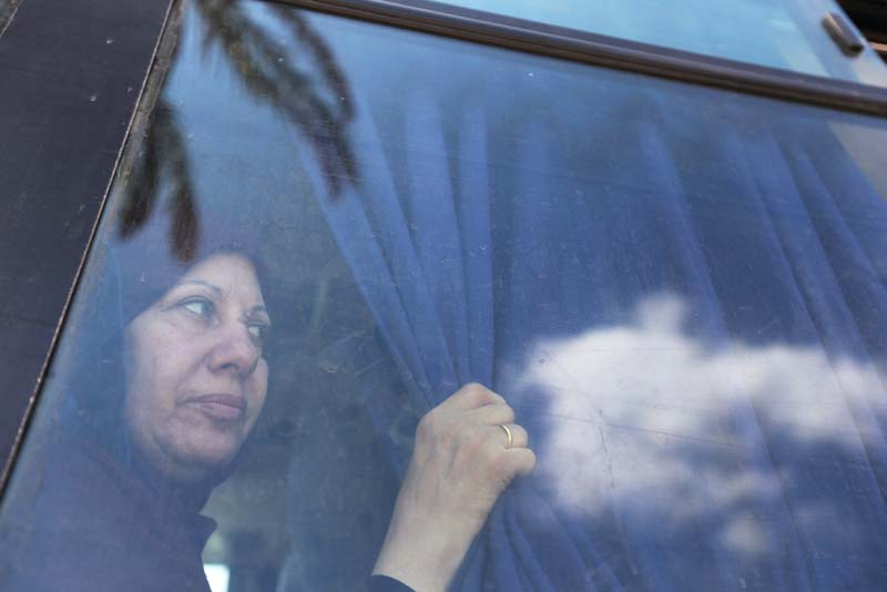 A Palestinian woman looks out of a bus window as she waits to cross into Egypt through the Rafah border crossing after it was opened by Egyptian authorities, in the southern Gaza Strip, on September 6, 2016. Photo: Reuters