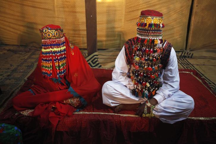 A bride and groom sit together during a mass marriage ceremony held in Karachi January 2, 2015. REUTERS/Athar Hussain/Files