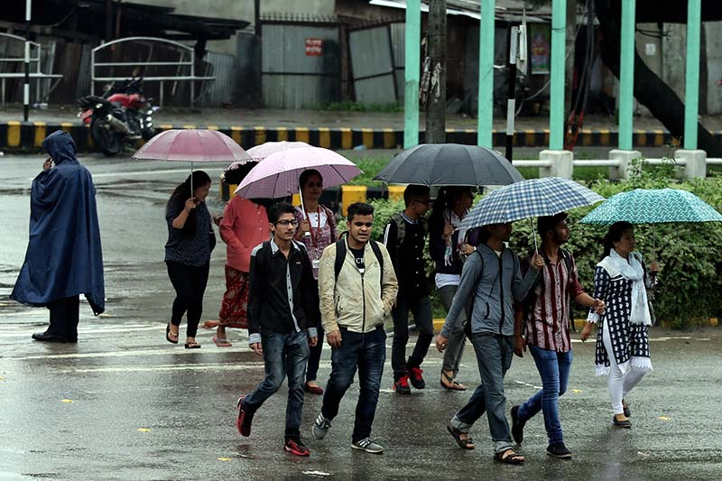 People carry umbrellas in the rain while crossing the road, at Baneshwor in Kathmandu, on Monday, September 12, 2016. Photo: RSS