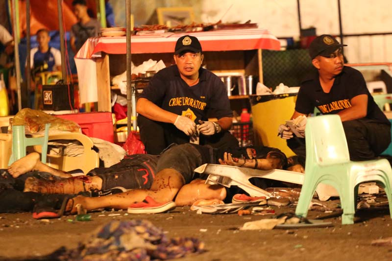 Philippine police investigators check bodies at a blast site at a night market that has left at least several people dead and wounded others in southern Davao city, Philippines on Friday September 2, 2016. Photo: AP