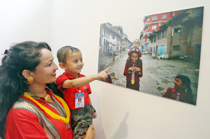 A kid points to a photo put on display at the Nepal Art Council, Babarmahal, on Friday, September 2, 2016. Photo: RSS